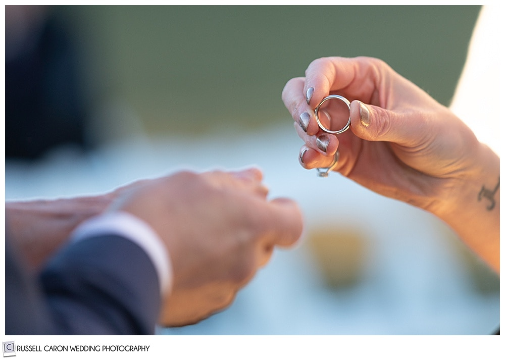 bride's fingers holding groom's wedding band