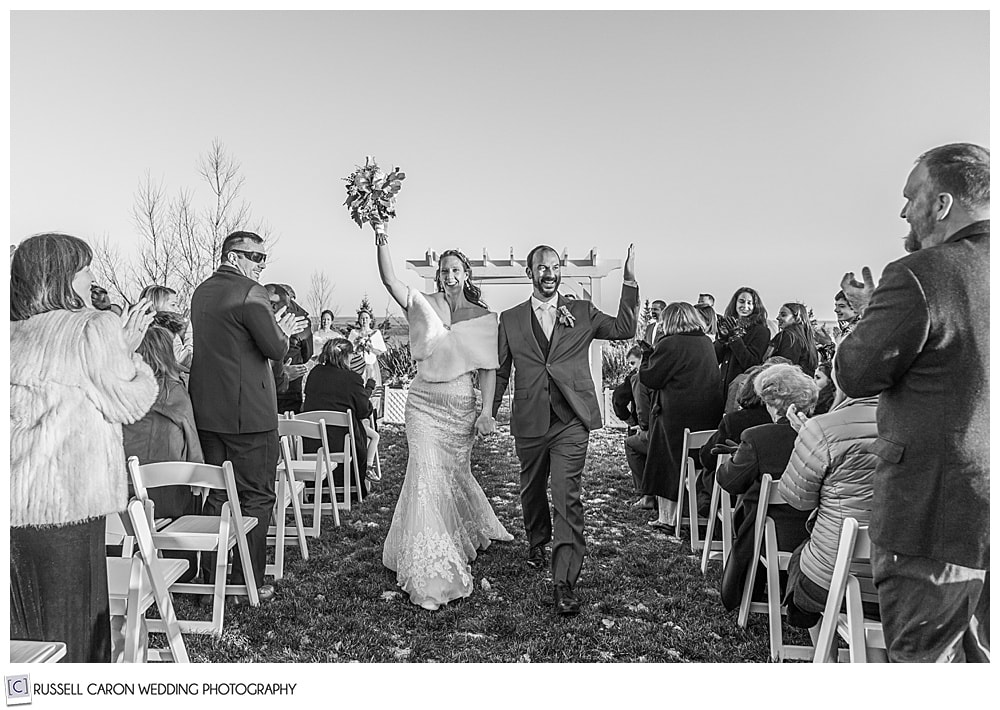 black and white photo of bride and groom during the recessional of their midcoast maine wedding ceremony