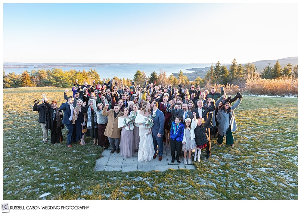bride and groom surrounded by family and friends during their midcoast maine wedding at north port, maine