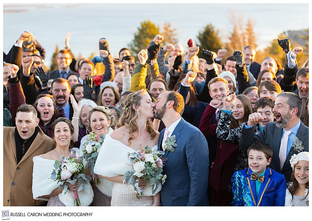 bride and groom kissing while their friends and family cheer, at their midcoast maine wedding, northport, maine