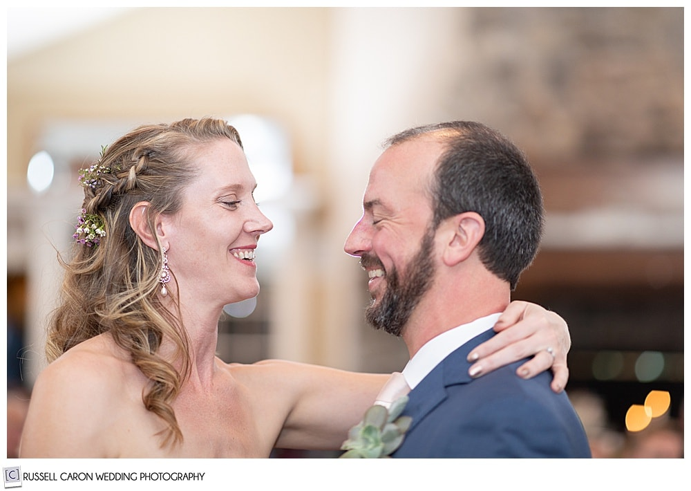 bride and groom smiling at each other during their first dance, at their midcoast maine wedding reception