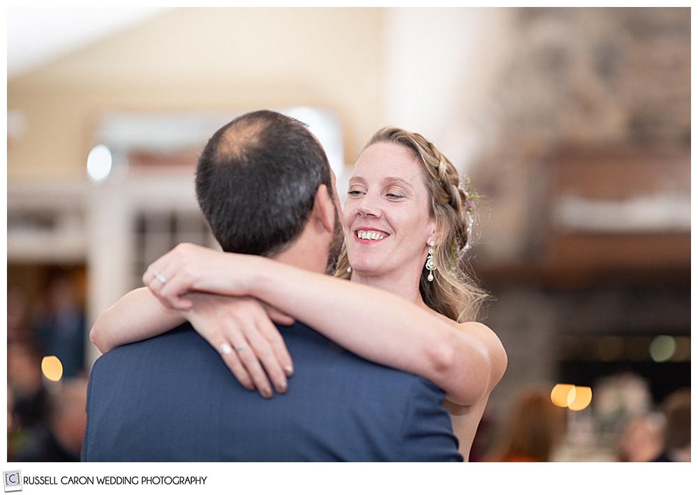 bride smiling at her groom during their first dance at their midcoast maine wedding reception