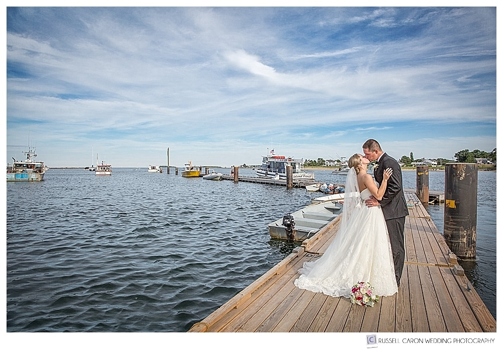 Bride and groom kissing on the dock at Camp Ellis Maine