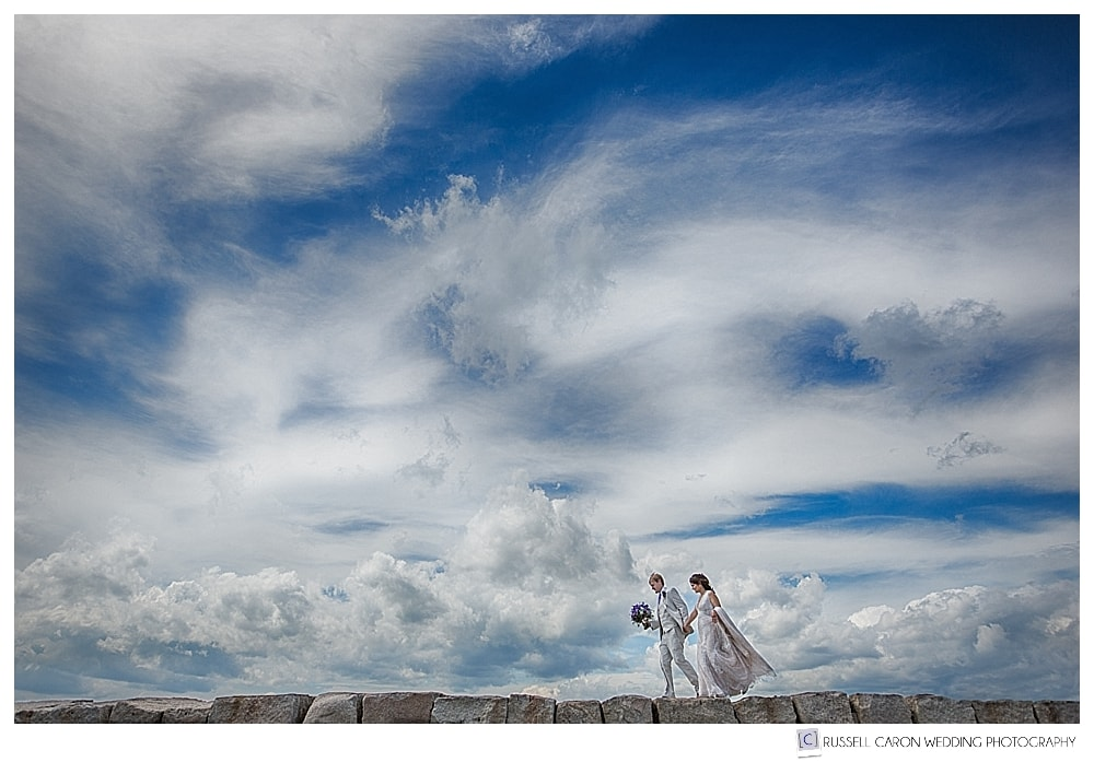 Bride and groom walking on the Kennebunkport Maine Breakwater