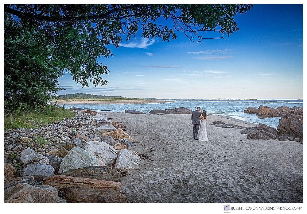 Bride and groom walking on the beach at the Small Point Club, Phippsburg, Maine