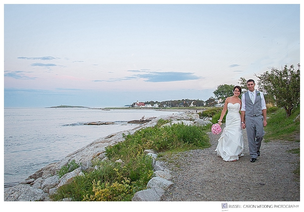 Bride and groom walking along the shore at Popham Beach, Maine