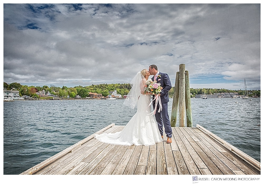 Bride and groom kissing on the dock Boothbay Harbor Maine