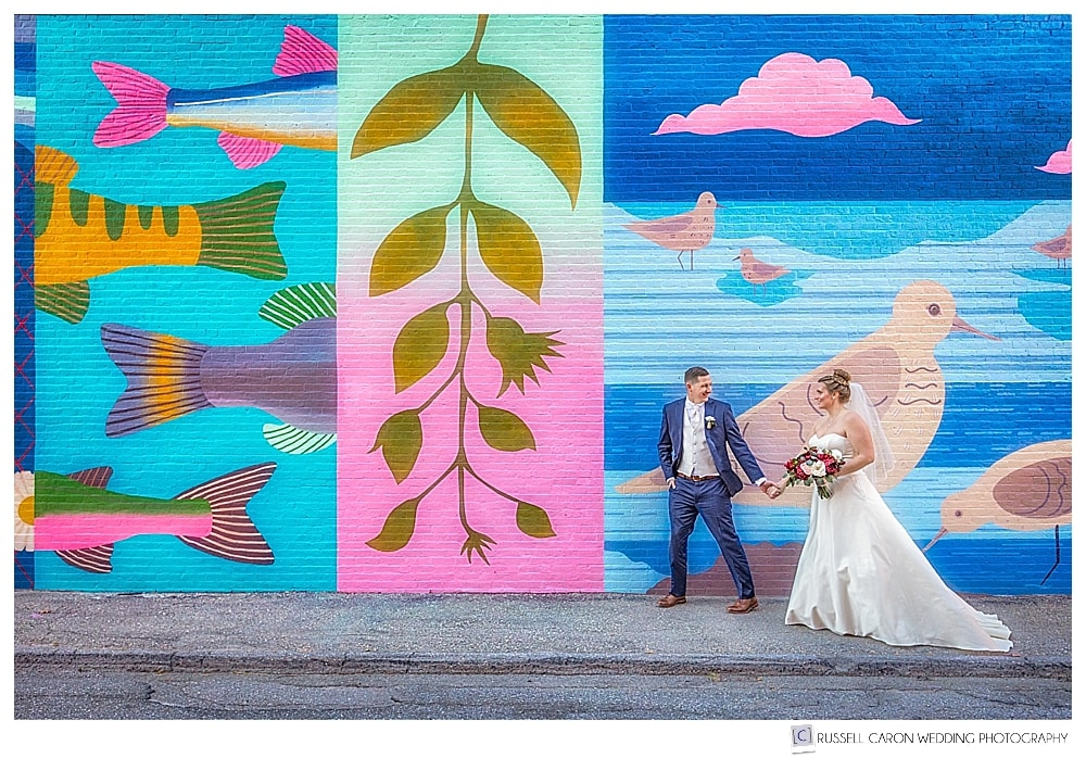 Bride and groom in front of wall mural on the Grasshopper Shop in Rockland Maine