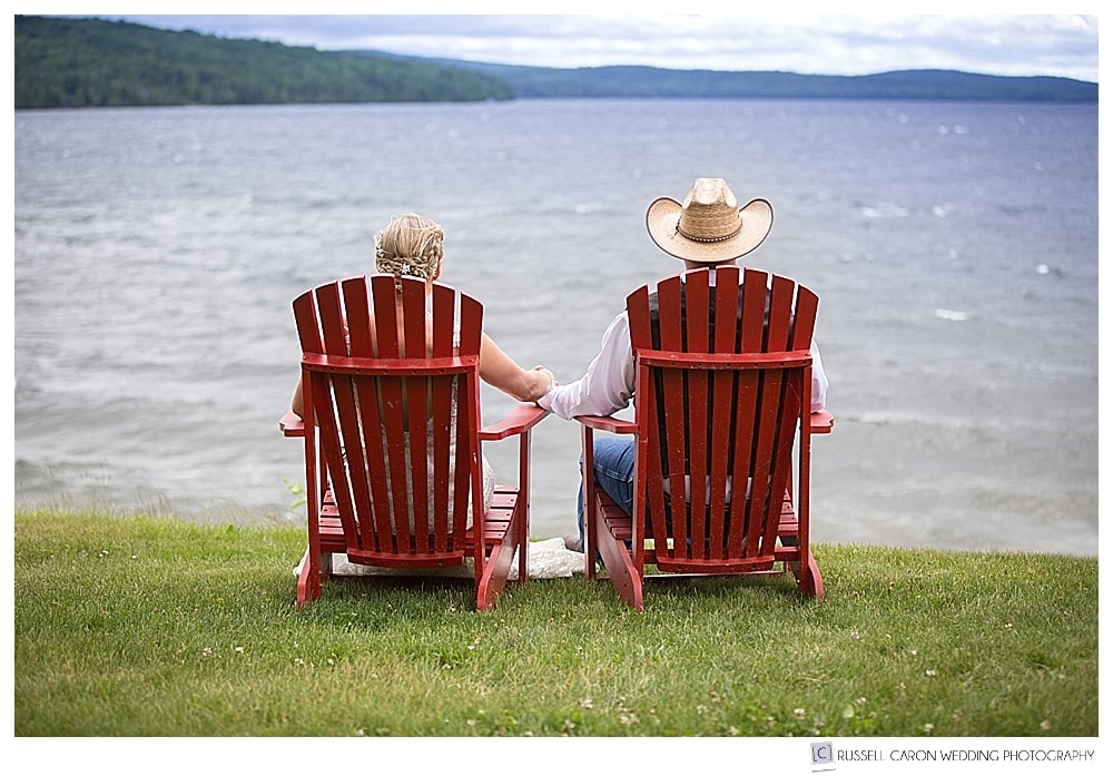 Bride and groom sitting in adirondack chairs at Rangeley Lake, maine