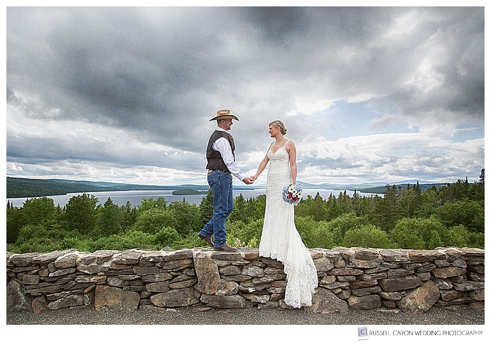 Bride and groom on a stone wall at Rangeley Lake, Maine