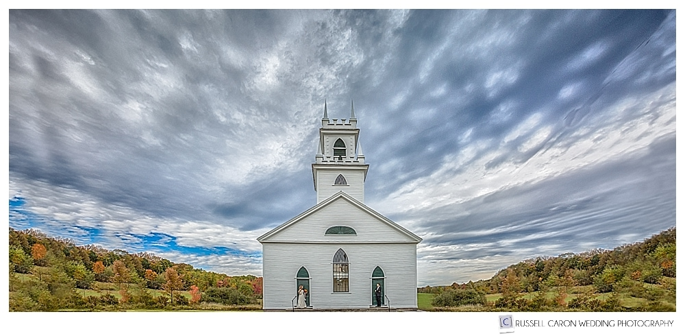 Bride and groom standing in front of a quaint New England white clapboard church in Norway, maine