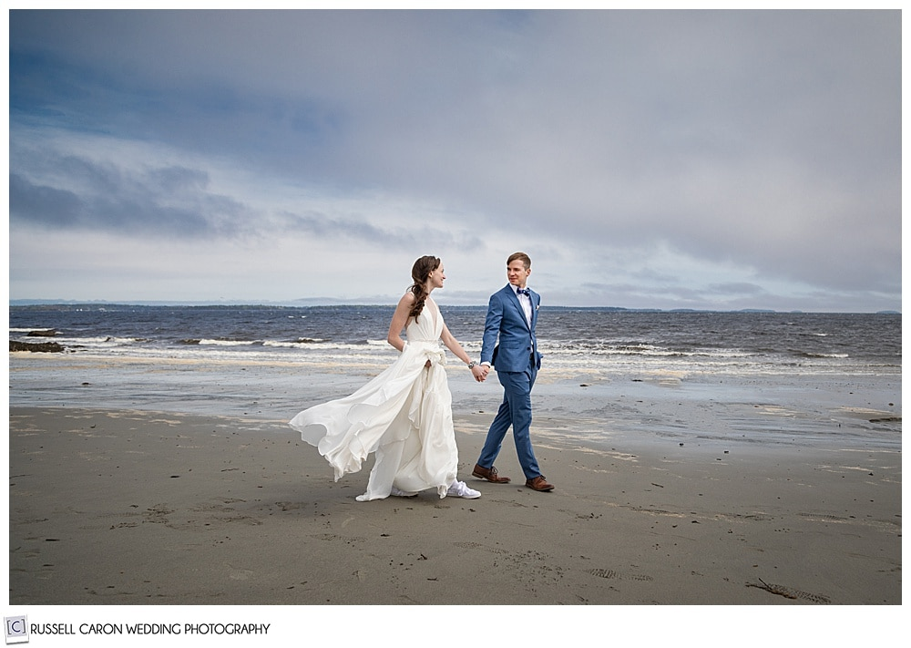 bride and groom walking hand-in-hand on the beach with dark skies