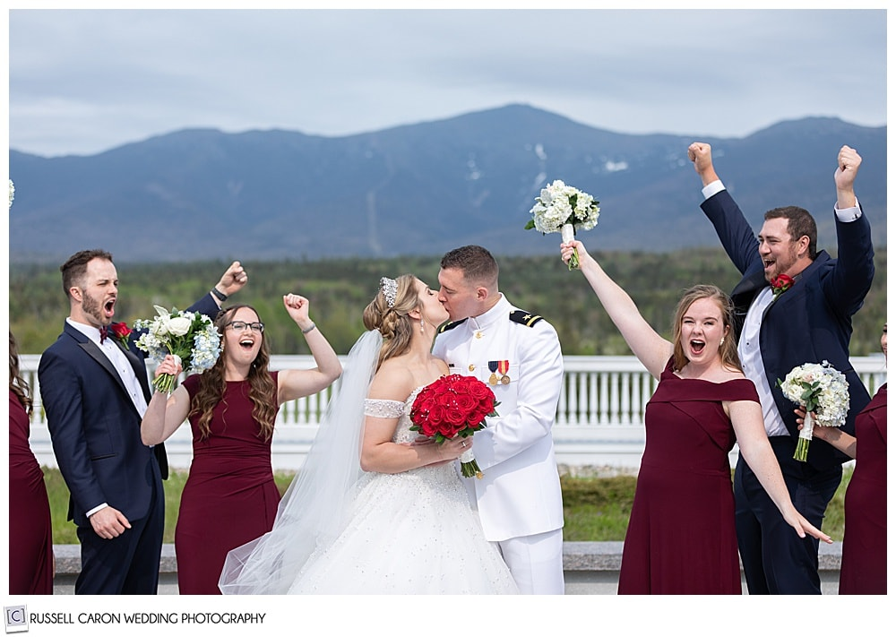 bride and groom kissing while bridal party cheers, at the Omni Mt. Washington Resort, Bretton Woods, New Hampshire