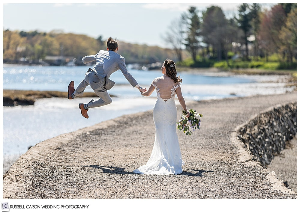 bride and groom walking hand-in-hand, away from the camera, on a path near the water, while the groom jumps and clicks his heels together