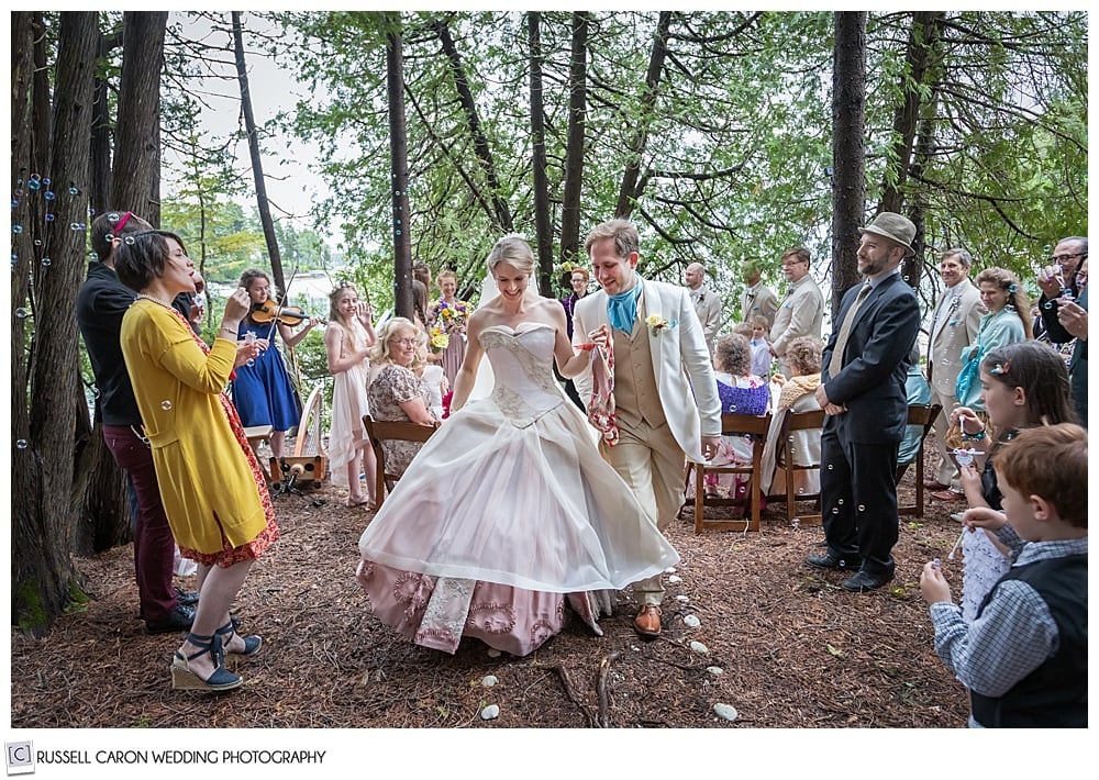 bride and groom, holding hand during their recessional in the woods, while guests blow bubbles