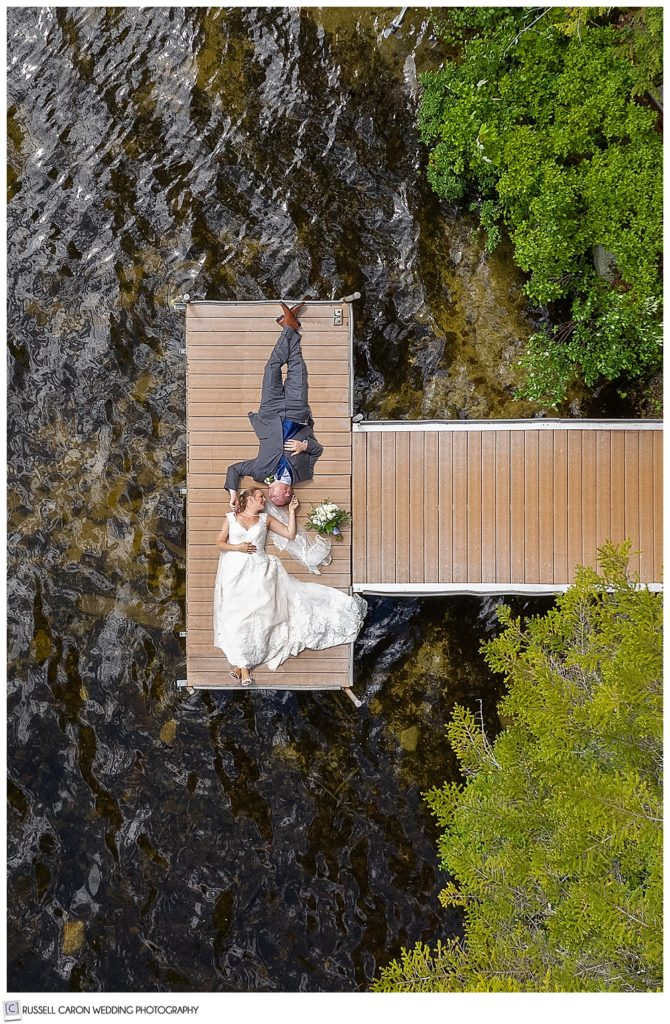 maine wedding photography team captures a maine drone wedding photo of a bride and groom laying on a dock