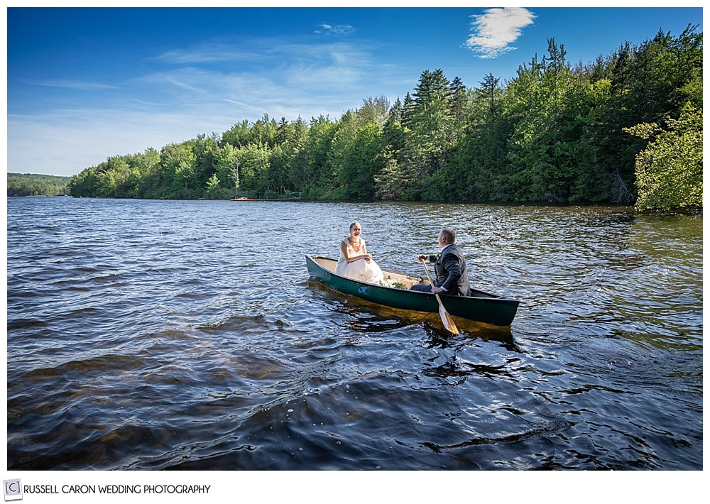 bride and groom in a canoe, with rough water, and blue skies