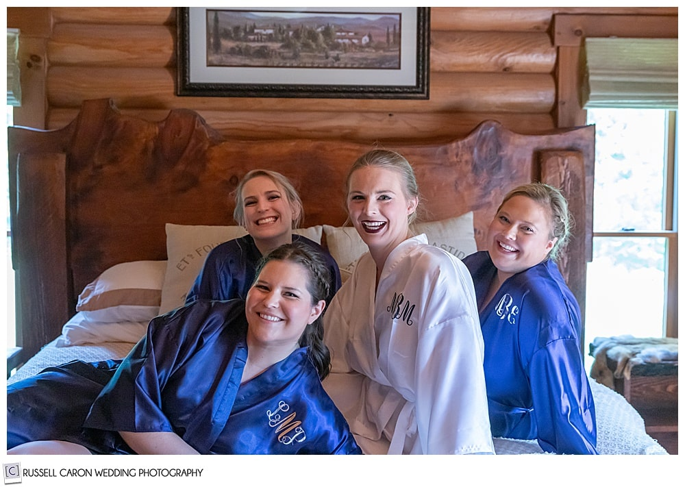 bride and bridesmaids on robes on a bed