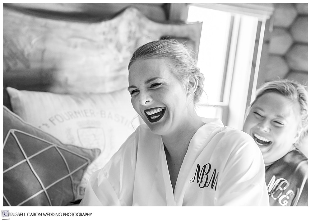 black and white photo of bride laughing with bridesmaid