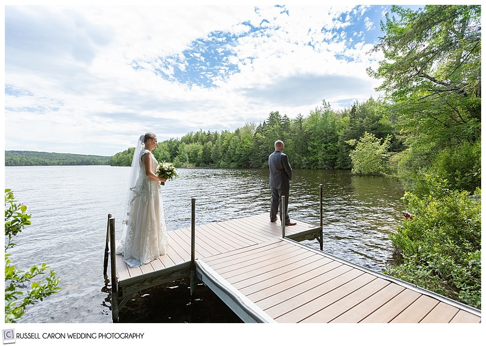 groom stands on a dock with his back to his bride