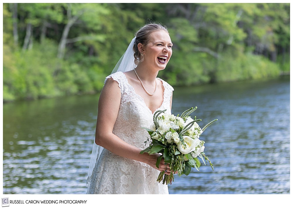 bride standing near a lake, smiling