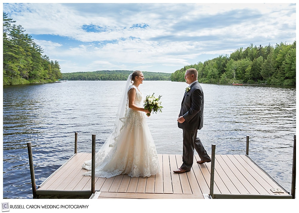 bride and groom on a dock in a lake, walking towards each other during a first look