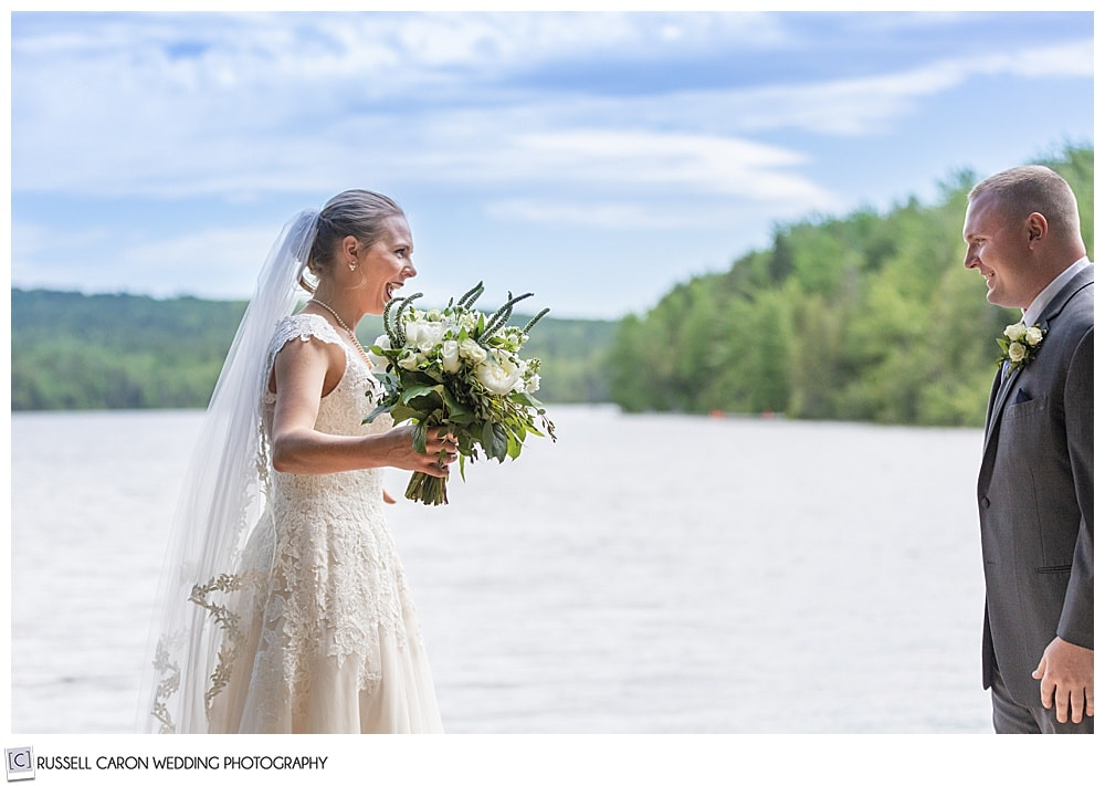bride standing on a dock on a lake, smiling