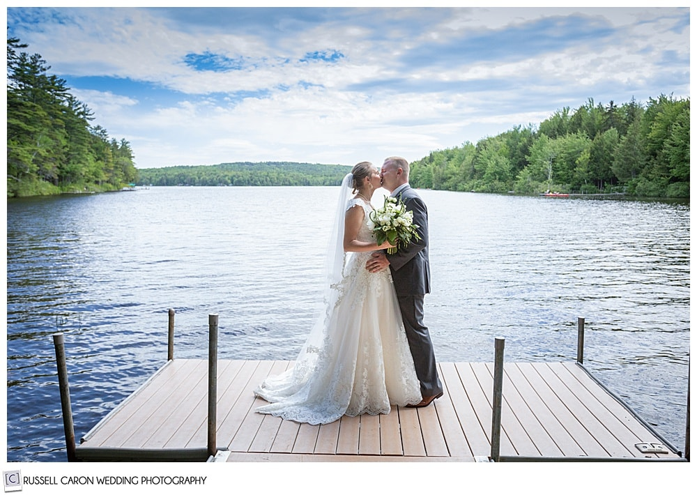 bride and groom kissing on a dock on a lake