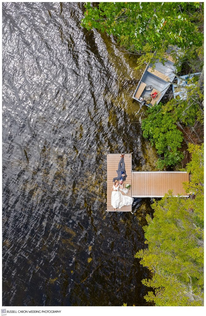 drone photo of bride and groom on a dock on a lake