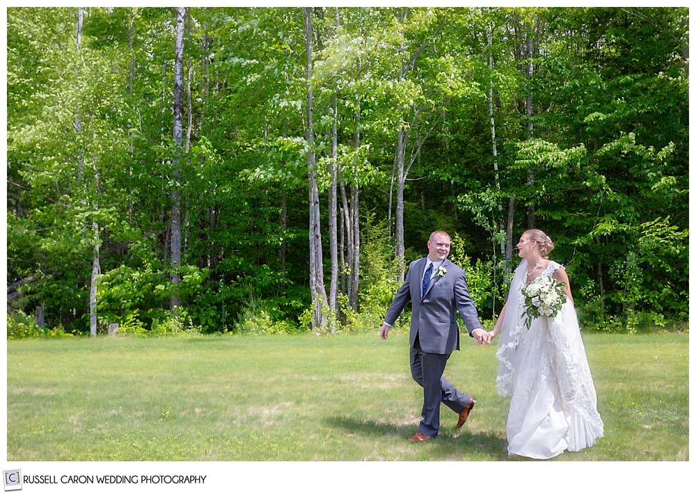 bride and groom holding hands, walking in a field