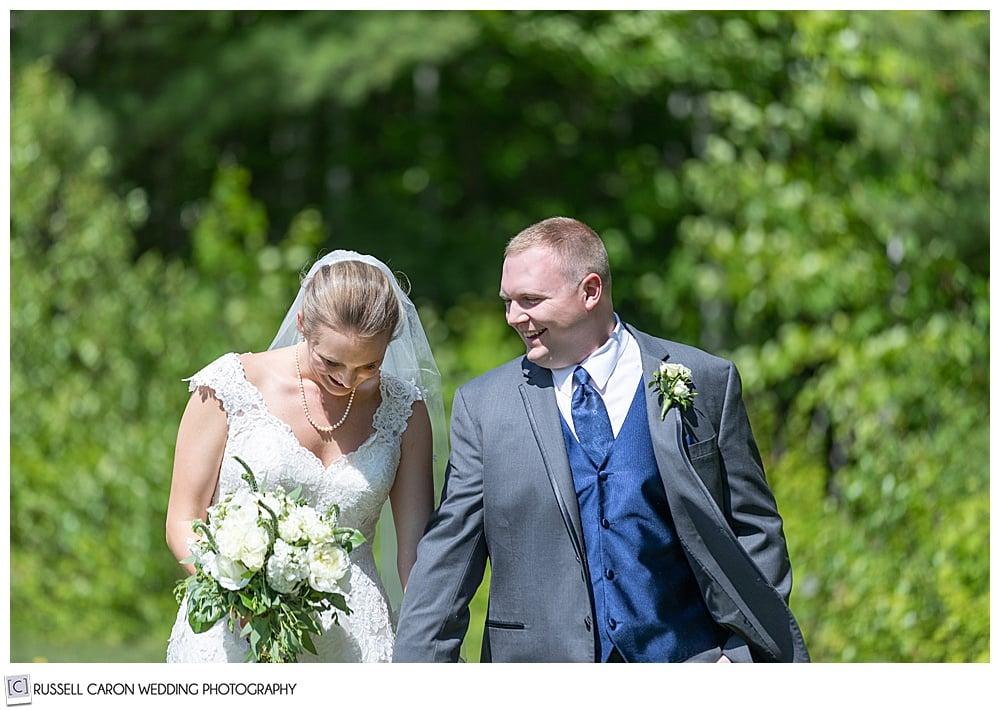 bride and groom walking side by side, groom looking at bride, bride looking down