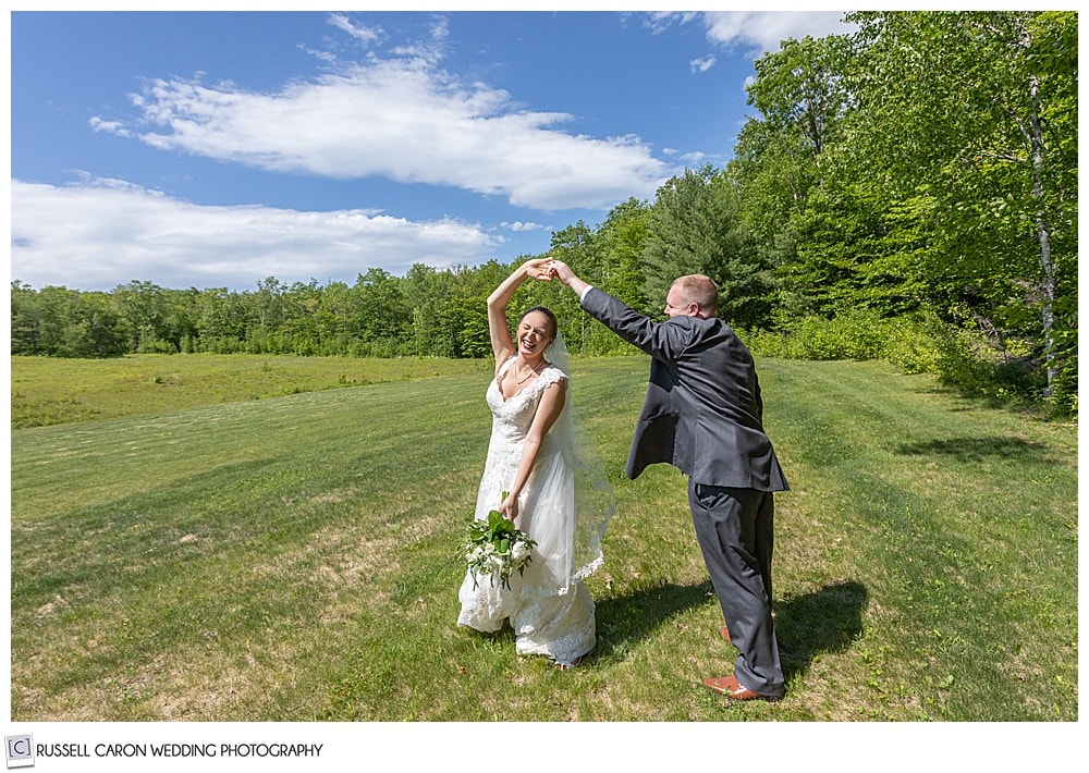 bride and groom twirling and laughing in a field
