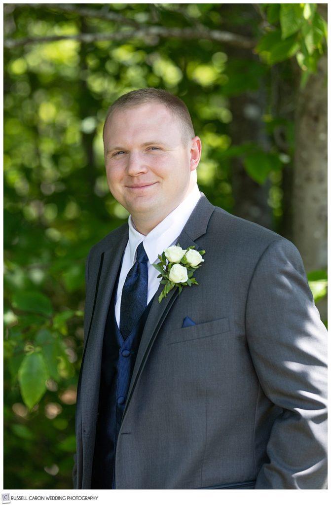 portrait of a groom wearing a dark gray suit