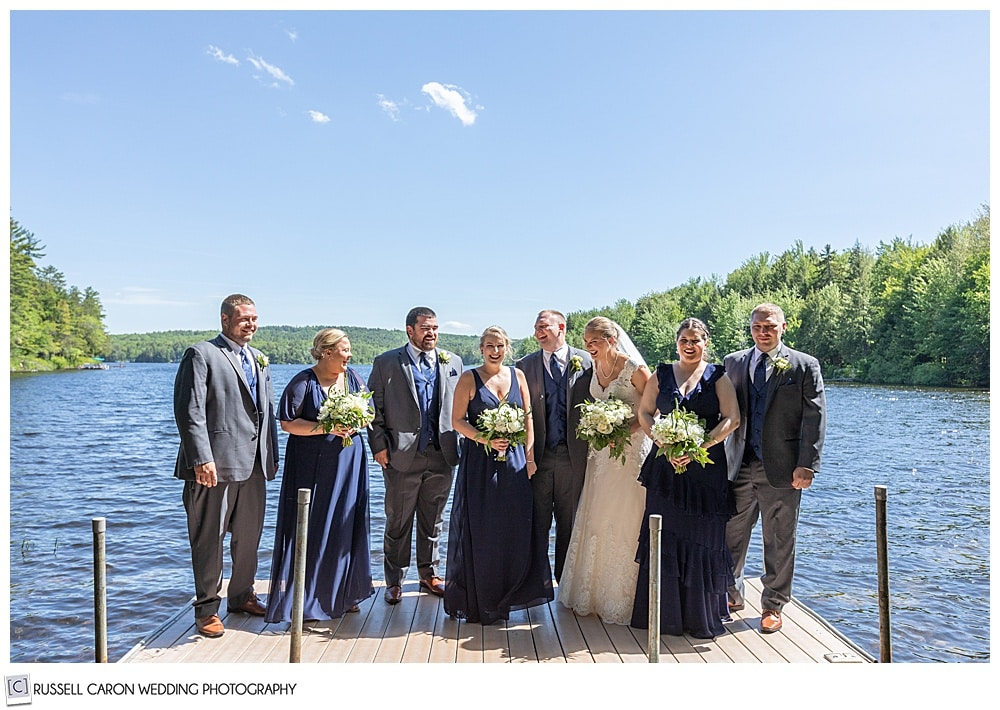 bridal party at the end of a dock on a lake in maine