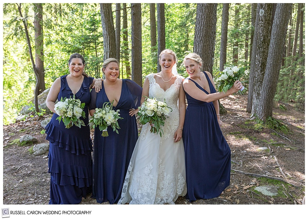 bride and bridesmaids laughing in the woods