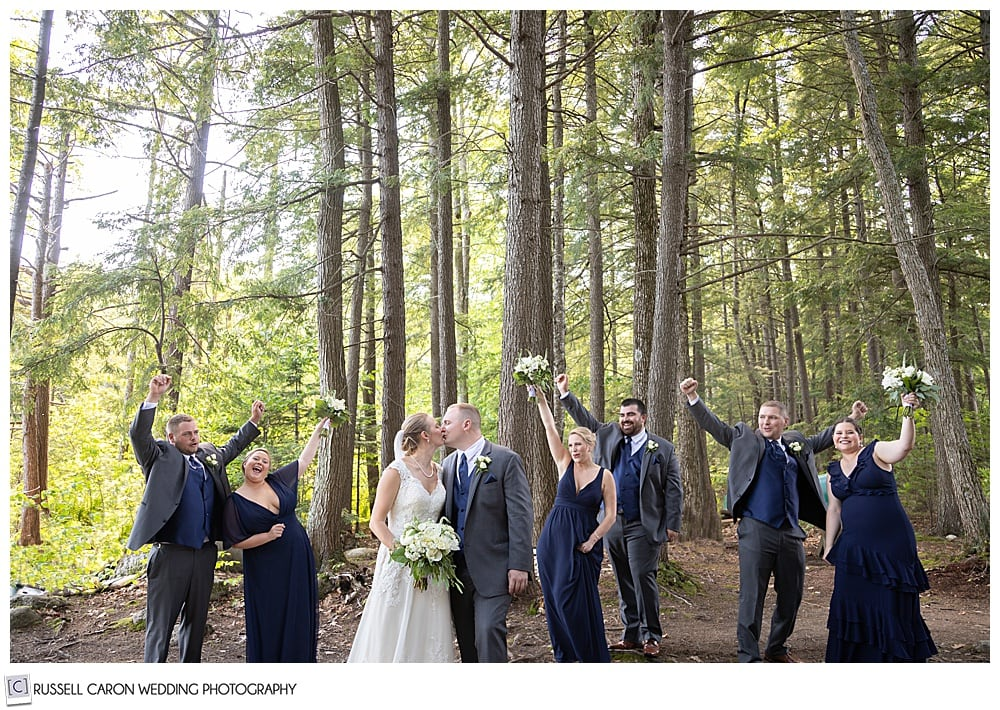 photo of bridal party in the woods, bride and groom kissing, everyone cheering