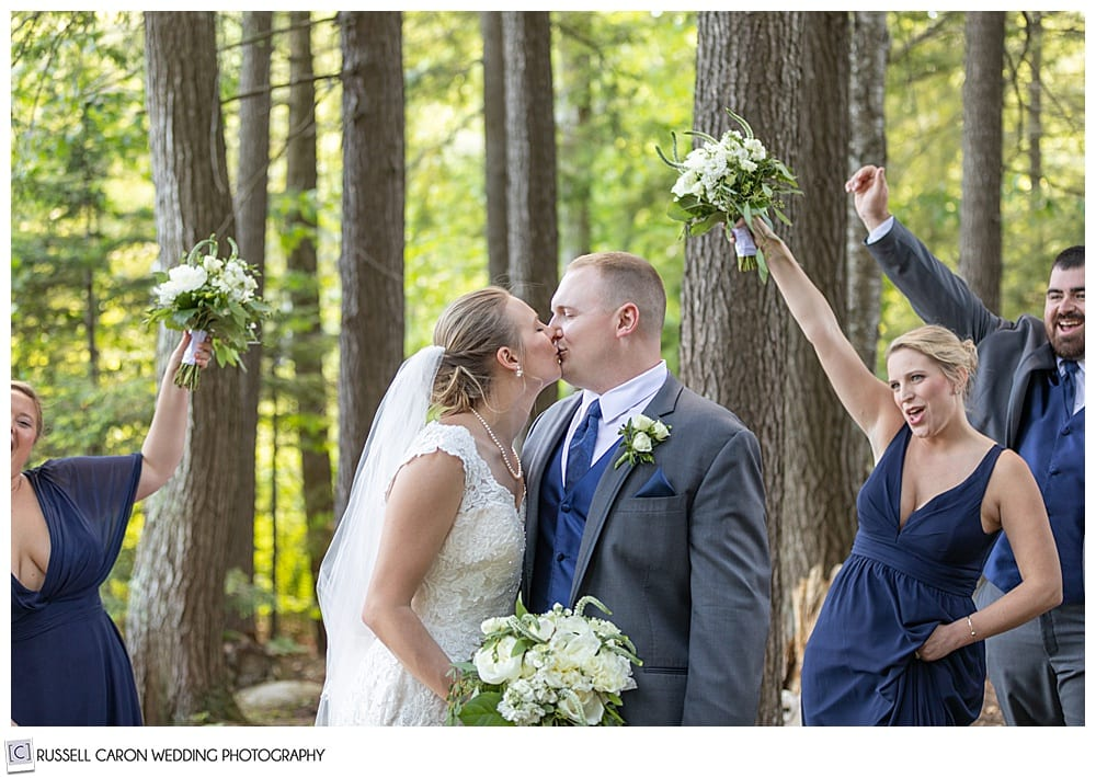 bride and groom in the woods, kissing, while bridal party cheer