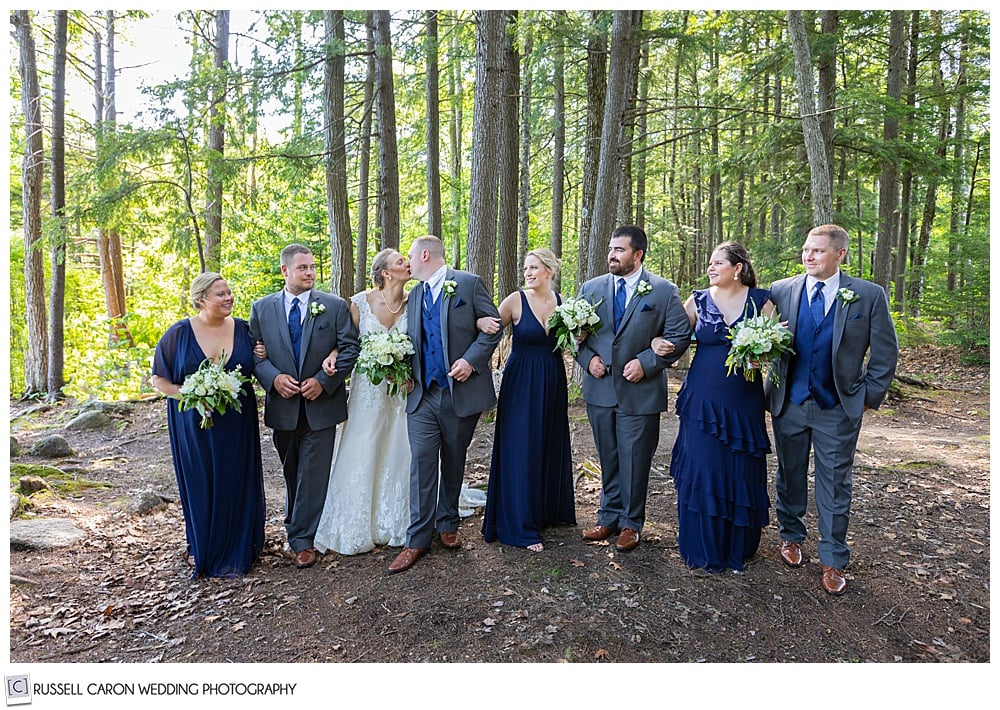 bridal party walking in the woods, arm in arm, while bride and groom kiss