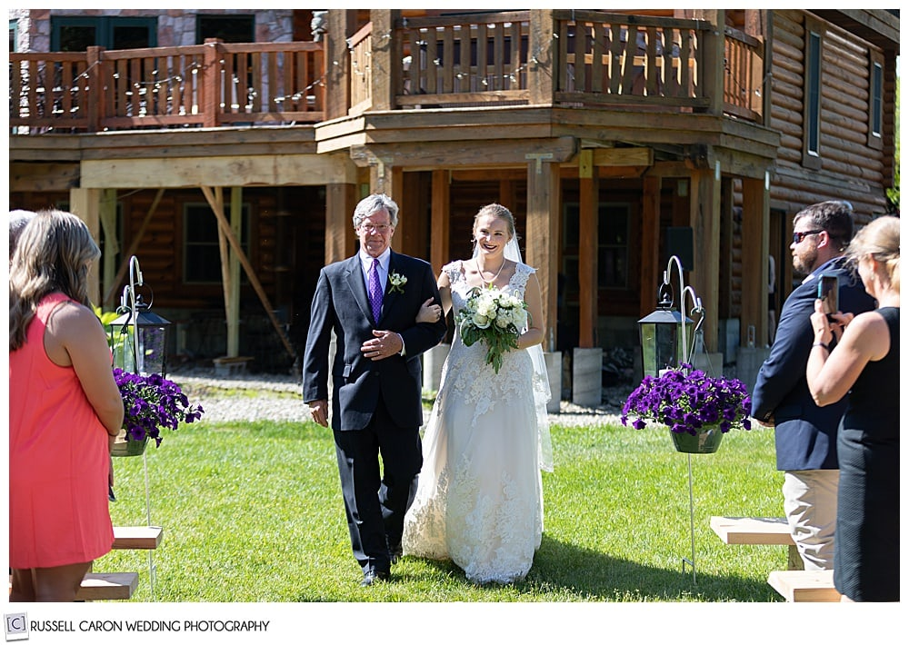 bride and her father walking towards the ceremony site in a back yard wedding