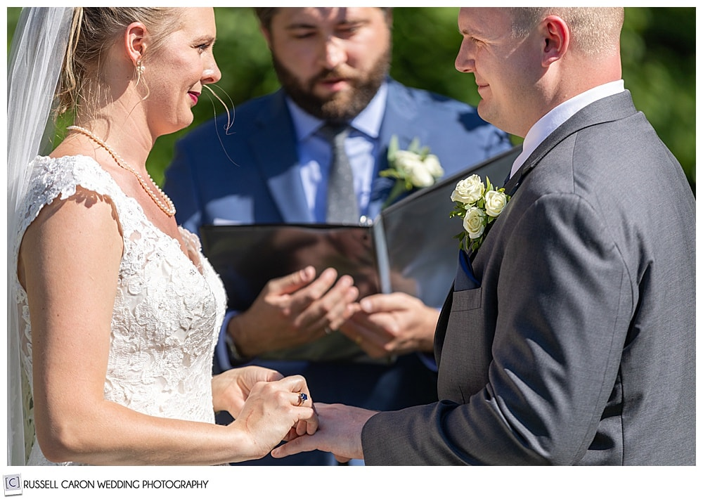 bride putting ring on the groom