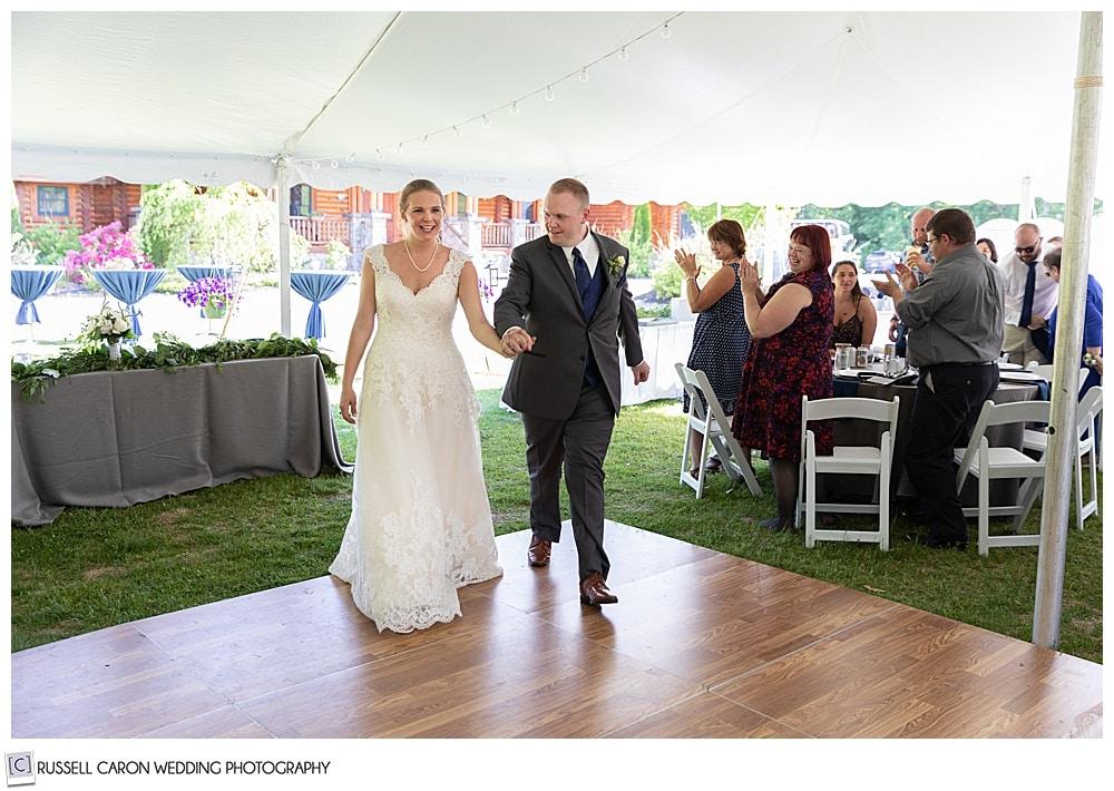 bride and groom walking onto a dance floor