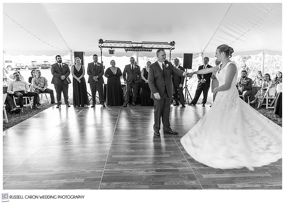 black and white photo of groom twirling bride on the dance floor