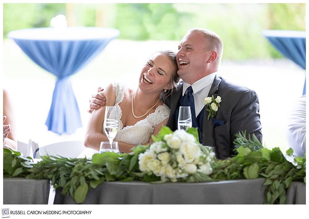 groom hugging bride as she sits next to him, both are laughing