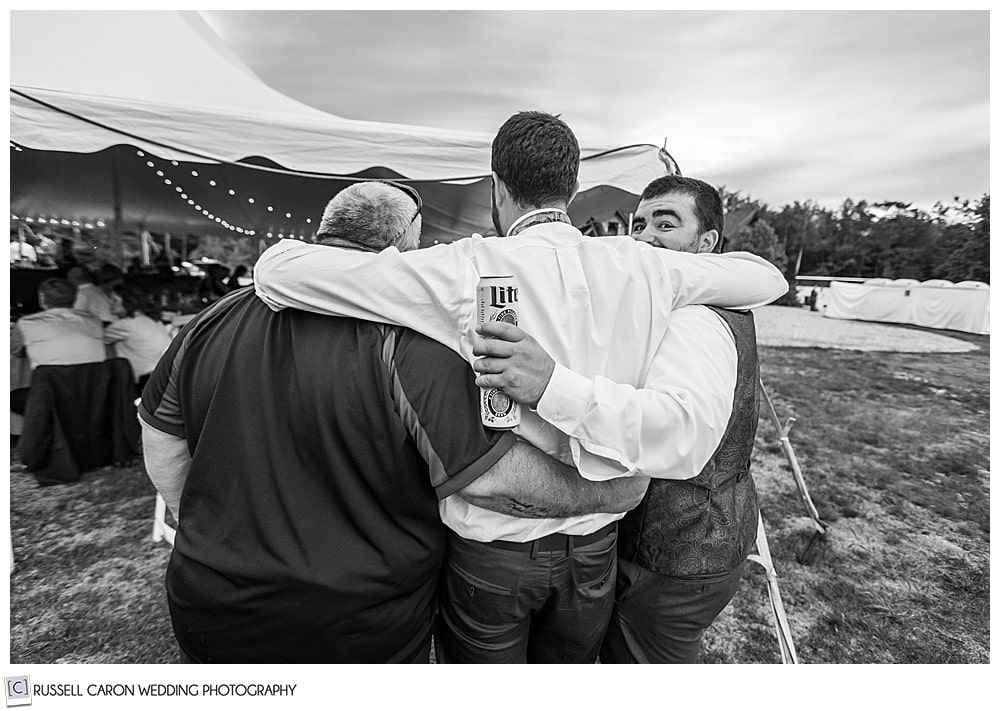 black and white photo of three guys hugging , their backs are to the camera