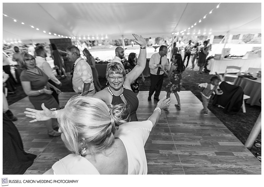 black and white photo of people dancing under an event tent