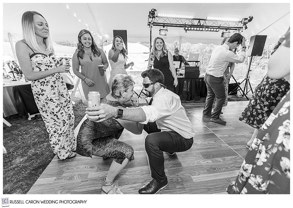 black and white photo of two people dancing, crouched down toward the dance floor
