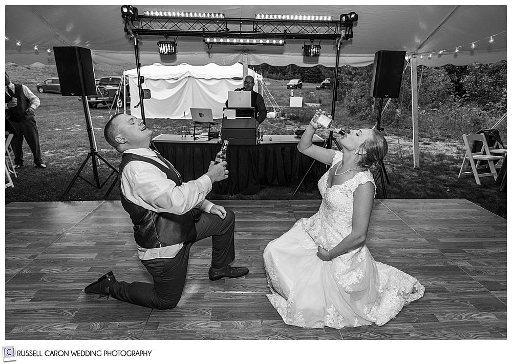 black and white photo of bride and groom, each with one knee on the dance floor, chugging a beverage
