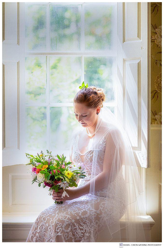 a serene bridal portrait of a bride sitting by a window
