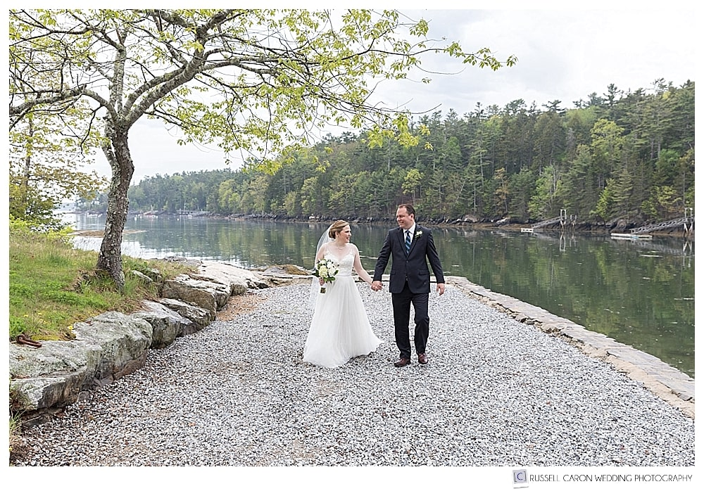 bride and groom walking hand in hand during their late spring boothbay harbor wedding