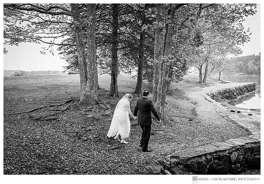 black and white photo of bride and groom walking together in barrett park boothbay harbor maine